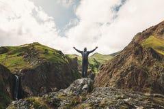 Glücklicher Forscher Young Man Standing mit den angehobenen Armen in den Sommer-Bergen, hintere Ansicht Lizenzfreie Stockfotografie