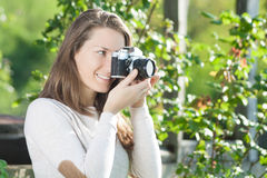 Glücklicher Fotograf der jungen Frau, der alte Kamera verwendet Lizenzfreies Stockbild