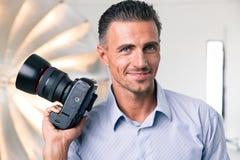 Glücklicher Fotograf, der Kamera hält Stockfotos