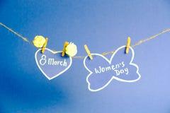 Glücklicher Frauen ` s Tag Frauen ` s Tag auf dem Papier, hängend an einem Seil mit Herzen und an den Blumen auf blauem Hintergru Stockbild