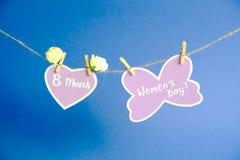 Glücklicher Frauen ` s Tag Frauen ` s Tag auf dem Papier, hängend an einem Seil mit rosa Herzen und an den Blumen auf blauem Hint Stockfotos