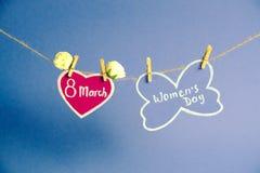 Glücklicher Frauen ` s Tag Frauen ` s Tag auf dem Papier, hängend an einem Seil mit rosa Herzen und an den Blumen auf blauem Hint Stockfoto