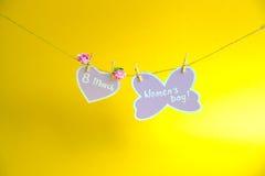 Glücklicher Frauen ` s Tag Frauen ` s Tag auf dem Papier, hängend an einem Seil mit rosa Herzen und an den Blumen auf goldenem Hi Stockfotografie