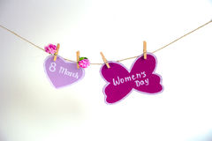 Glücklicher Frauen ` s Tag Frauen ` s Tag auf dem Papier, hängend an einem Seil mit rosa Herzen und an den Blumen auf weißem Hint Lizenzfreie Stockfotografie