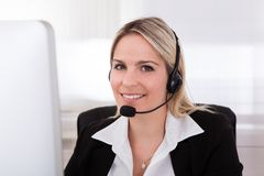Glücklicher Frauenbetreiber mit Kopfhörer Stockfotografie