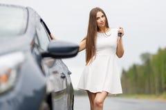 Glücklicher Frauenfahrer, der Autoschlüssel auf Autotür zeigt Stockfoto