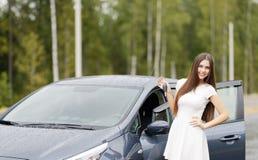 Glücklicher Frauenfahrer, der Autoschlüssel auf Autotür zeigt Stockfotografie