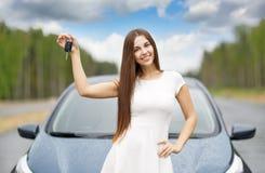 Glücklicher Frauenfahrer, der Autoschlüssel auf Autotür zeigt Lizenzfreie Stockfotos