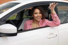 Glücklicher Frauenfahrer, der Autoschlüssel zeigt und auf Autotür sich lehnt lizenzfreies stockfoto