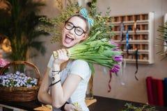 Glücklicher Frauenflorist, der Bündel purpurrote Tulpen und Blinzeln hält Lizenzfreie Stockfotografie