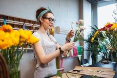 Glücklicher Frauenflorist, der Blumen hält und Blumenstrauß im Shop macht Stockbilder