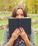Glücklicher Frauenmesswert Mädchen, das über altem Buch auf Herbsthintergrund schaut Stockfotografie
