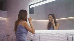 Glücklicher Frauenreinigungszahn mit Bürste im Badezimmer Tragender Zahn der Nahaufnahmeperson stock video footage