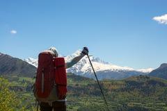 Glücklicher Frauenreisender mit den offenen Armen steht auf der Gebirgsplatte Lizenzfreie Stockfotos