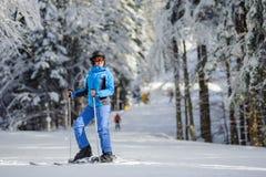 Glücklicher Frauenskifahrer auf einer Skisteigung im Wald Lizenzfreies Stockbild