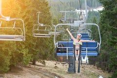 Glücklicher Frauenskifahrer hat Spaß auf Skiaufzug und reitet bis zur Spitze des Berges und zeigt sich Daumen mit Skis Lizenzfreies Stockbild