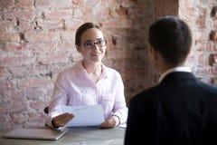 Glücklicher Frauenstunden-Manager mit der Zusammenfassung, die Arbeitssuchenden betrachtet stockfotografie