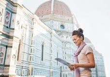 Glücklicher Frauentourist, der die Karte in Florenz, Italien betrachtet Stockbild