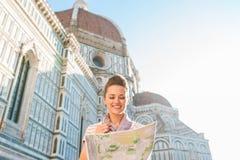Glücklicher Frauentourist, der Karte bei der Stellung des nahen Duomo betrachtet Lizenzfreie Stockfotografie