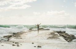 Glücklicher Frauentourist, der Wellen von stürmischem Mittelmeer genießt stockfotografie