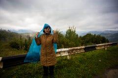 Glücklicher Frauentourist 60 Jahre alt im Regenmantel, der schöne Ansicht von Bergen genießt Stockbild
