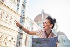 Glücklicher Frauentourist mit Karte zeigend auf etwas, Florenz Stockfotografie