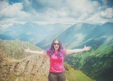 Glücklicher Frauenwanderer, der auf die Oberseite des Berges im Freien steht stockbilder