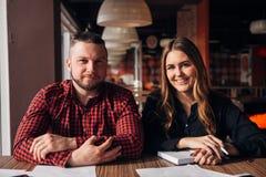 Glücklicher Freiberufler zwei, der an der Kamera im Café lächelt Stockbilder