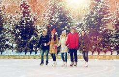 Glücklicher Freundeislauf auf Eisbahn draußen lizenzfreie stockbilder