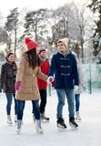 Glücklicher Freundeislauf auf Eisbahn draußen Stockbilder