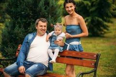 Glücklicher froher junger Familienvater, Mutter und kleine Tochter, die Spaß draußen, zusammen spielend im Sommerpark hat stockfotografie