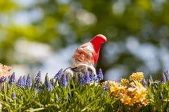 Glücklicher Gartenkobold mit Kaninchen am sonnigen Tag Stockfoto
