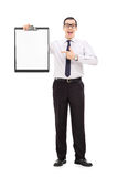 Glücklicher Geschäftskerl, der auf ein Klemmbrett zeigt Stockbild