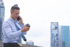 Glücklicher Geschäftsmann, der Anruf auf seinem Handy und Getränkkaffee macht lizenzfreie stockbilder