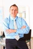 Glücklicher Geschäftsmann, der auf Büroschreibtisch sich lehnt stockbilder