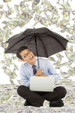 Glücklicher Geschäftsmann, der auf Boden mit US-Dollar Regen sitzt Lizenzfreie Stockfotografie
