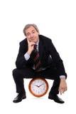 Glücklicher Geschäftsmann, der auf einer Borduhr sitzt lizenzfreies stockbild