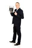 Glücklicher Geschäftsmann, der auf Taschenrechner zeigt Stockfoto