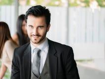 Glücklicher Geschäftsmann, der die Kamera, Büroangestellten, unternehmerische Entscheidungen betrachtet Stockbild