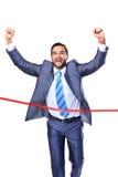 Glücklicher Geschäftsmann, der durch Ziellinie läuft Stockfotografie