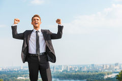 Glücklicher Geschäftsmann, der eine Trophäe bei der Stellung gegen schwarzen Hintergrund hält Stockfoto