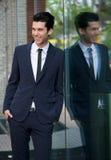 Glücklicher Geschäftsmann, der am Glasgebäude sich lehnt Stockfotos