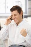 Glücklicher Geschäftsmann, der gute Nachrichten am Telefon erhält Stockbilder
