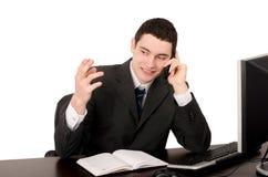Geschäftsmann, der am Schreibtisch spricht am Telefon sitzt. Stockfoto