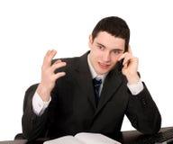 Geschäftsmann, der am Schreibtisch spricht am Telefon sitzt. Stockbilder