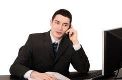 Geschäftsmann, der am Schreibtisch spricht am Telefon sitzt. Lizenzfreie Stockfotos