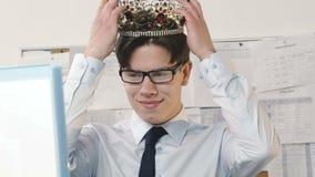 Glücklicher Geschäftsmann, der Krone auf Kopf in das Büro einsetzt stock video
