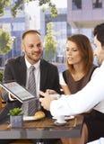 Glücklicher Geschäftsmann, der on-line-Nachrichten auf Tablette teilt Lizenzfreie Stockbilder