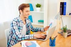 Glücklicher Geschäftsmann, der Papier mit diagrama hält und Laptop verwendet Lizenzfreie Stockfotos