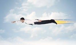 Glücklicher Geschäftsmann, der schnell auf den Himmel zwischen Wolken fliegt Stockfoto